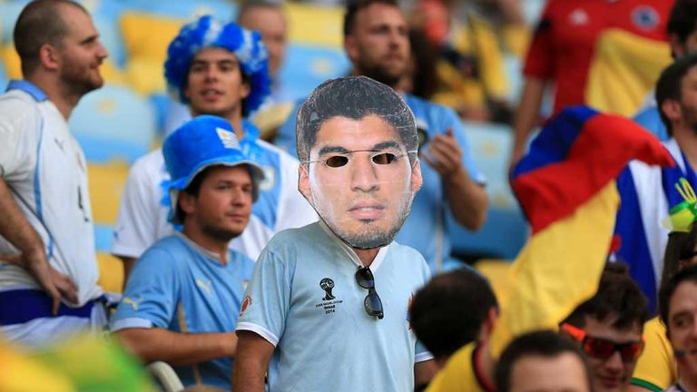 A Uruguay fan wears a Luis Suarez mask during the game against Colombia