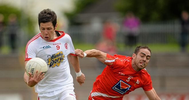 Tyrone captain Sean Cavanagh is challenged by John O'Brien