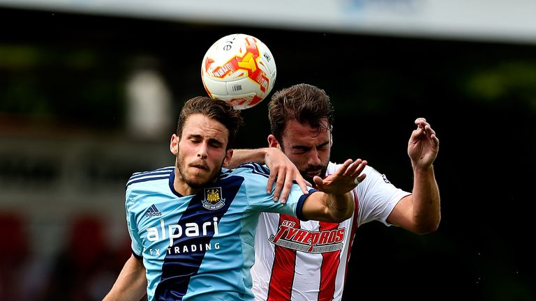 Diego Poyet of West Ham and Stevenage's Simon Walton vie for the ball