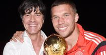 Joachim Low (l) and Lukas Podolski pose with the World Cup trophy