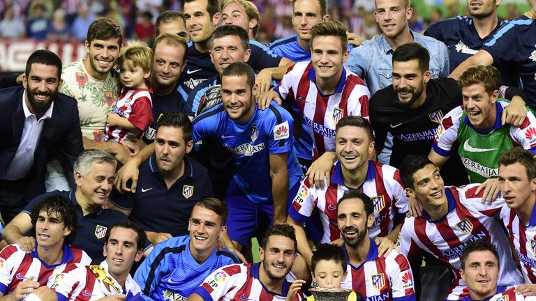 Atletico players show off the trophy