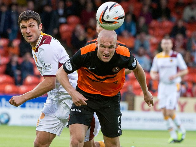 Motherwell's John Sutton chases Jaroslaw Fojut of Dundee United
