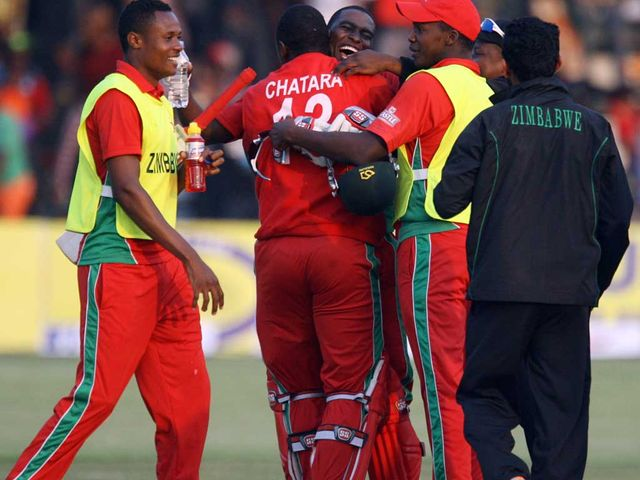 Zimbabwe captain Elton Chigumbura is mobbed by his players after victory over Australia