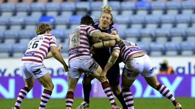 Eorl Crabtree (middle) is tacked by John Bateman and Tony Clubb during Huddersfield's 24-16 loss at Wigan on February 13