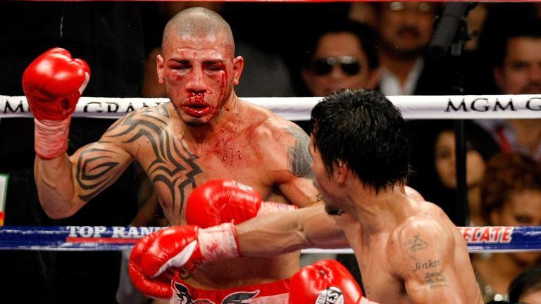 A bloodied Miguel Cotto is backed up by Manny Pacquiao in their WBO welterweight title clash in 2009