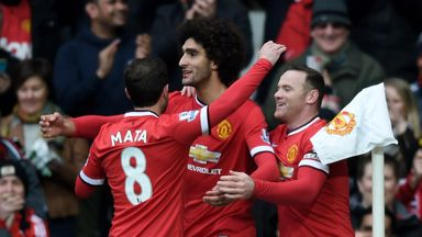 Marouane Fellaini (C) of Manchester United is congratulated by team-mates Juan Mata (L) and Wayne Rooney
