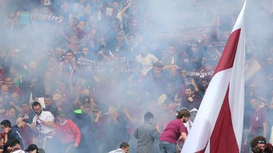 Torino fans react after a firework explodes during the Turin derby
