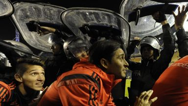River Plate players leave the pitch under police shields after the match