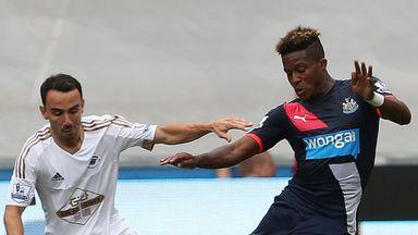 Leon Britton (L) vies for the ball with Newcastle