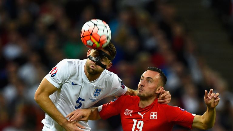 Gary Cahill of England heads the ball under pressure from Josip Drmic