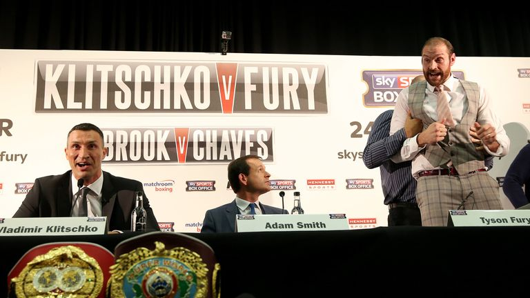 Fury (R) is restrained by father John after offering to fight Klitschko at a London press conference