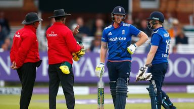 Ben Stokes of England waits for the decision of his wicket as Eoin Morgan of England watches