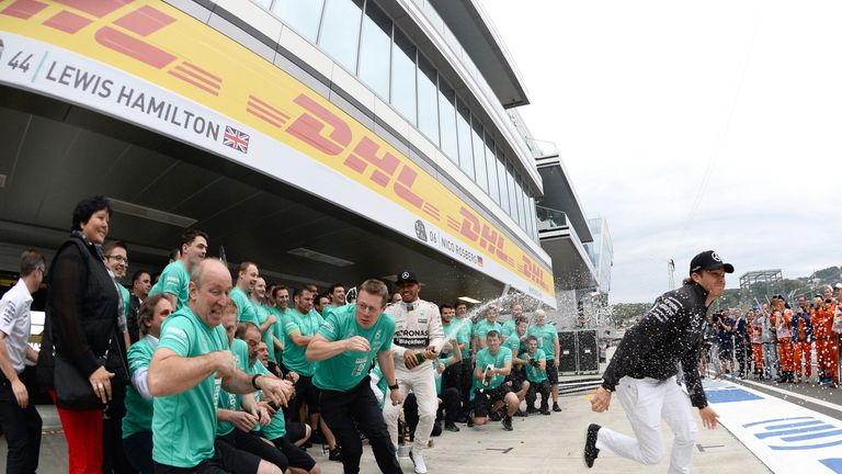 Nico Rosberg runs for cover as Lewis Hamilton sprays the champagne in Mercedes' post-race celebrations