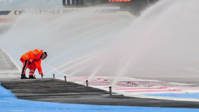 A marshal attends to the circuit's advanced sprinkler system