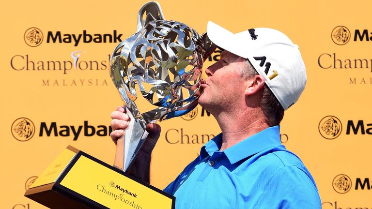 Marcus Fraser of Australia kisses the Maybank Championship Trophy after his win in Malaysia