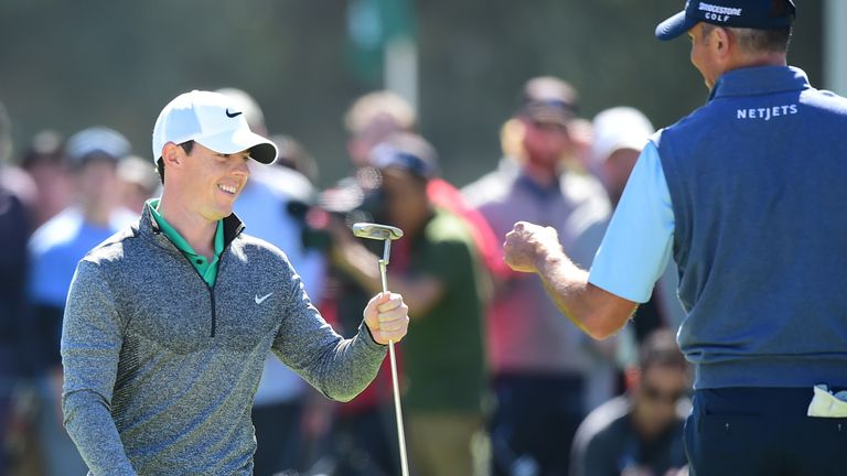 Rory McIlroy celebrates with Matt Kuchar after sinking a monster putt for birdie at the third