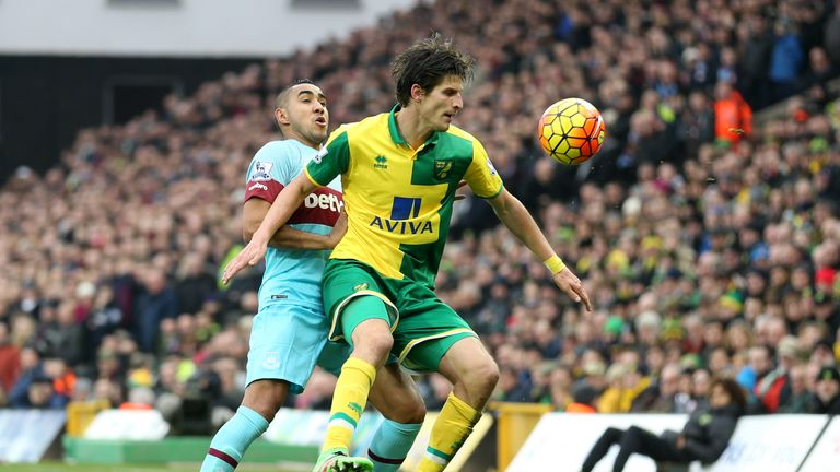 Norwich City's Timm Klose tussles with West Ham United's Dimitri Payet