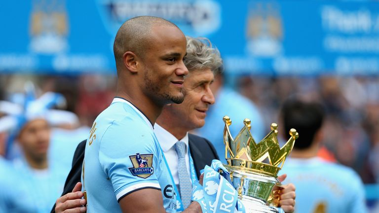 Vincent Kompany and Manuel Pellegrini celebrate with the Premier League trophy in 2014