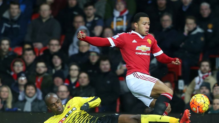 Memphis Depay attempts to avoid a challenge from Watford's Allan Nyom