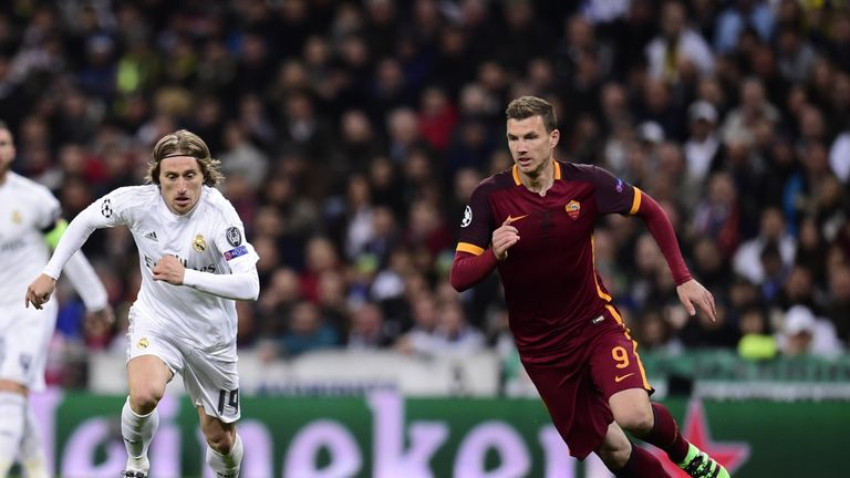Real Madrid's Luka Modric (left) vies with Roma's Edin Dzeko (right)