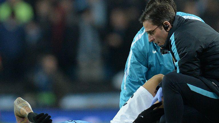 Manchester City defender Nicolas Otamendi (L) reacts as he receives medical treatment