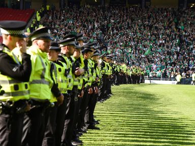 Police line the pitch at full-time after a fan invasion