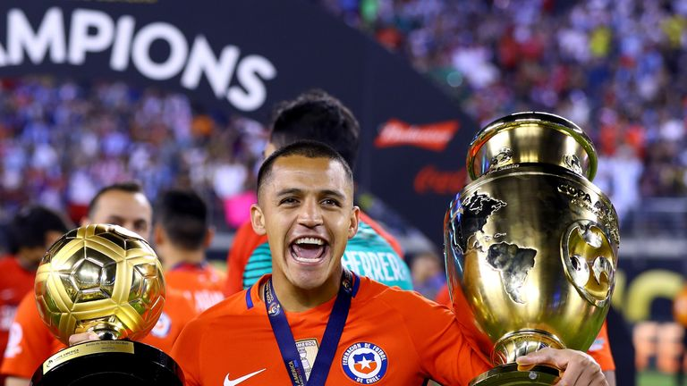 Alexis Sanchez celebrates with the Copa America trophy (R) and the Player of the Tournament award