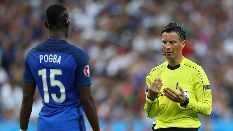 English referee Mark Clattenburg talks with Paul Pogba