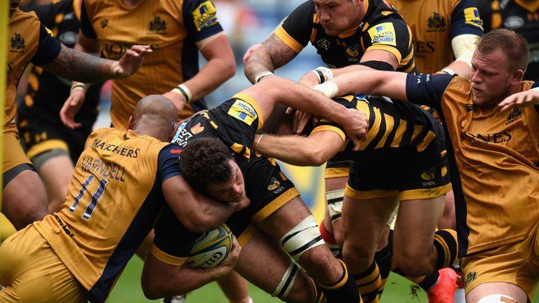 Alex Rieder of Wasps is tackled by Tom Varndell of Bristol