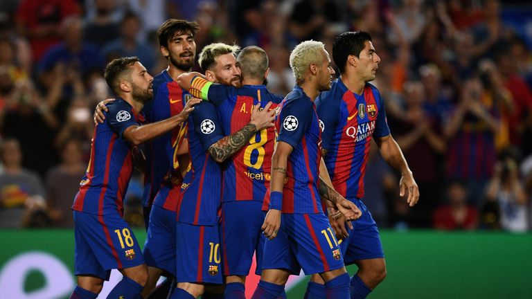 Messi is congratulated by his team-mates after scoring his third and his side's fifth goal