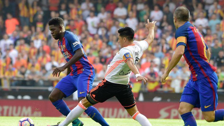 Barcelona defender Samuel Umtiti (L) vies with Valencia midfielder Enzo Perez (C)