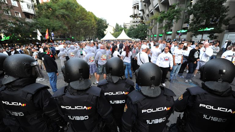 Riot police watch over Legia Warsaw fans outside the Santiago Bernabeu stadium