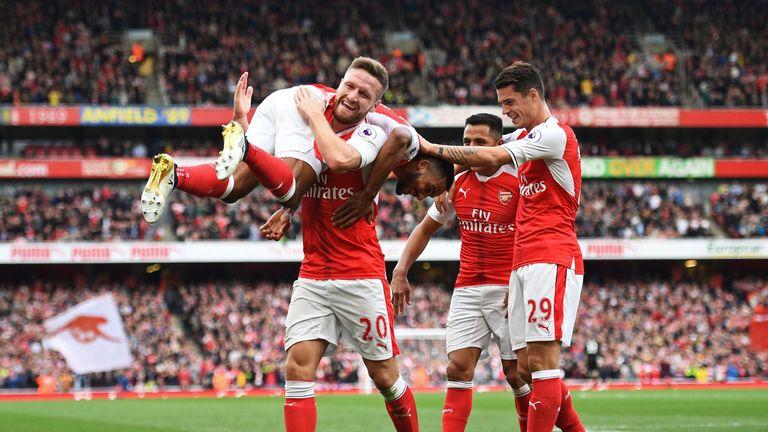 Shkodran Mustafi lifts Theo Walcott after the Arsenal forward's goal against Swansea last month