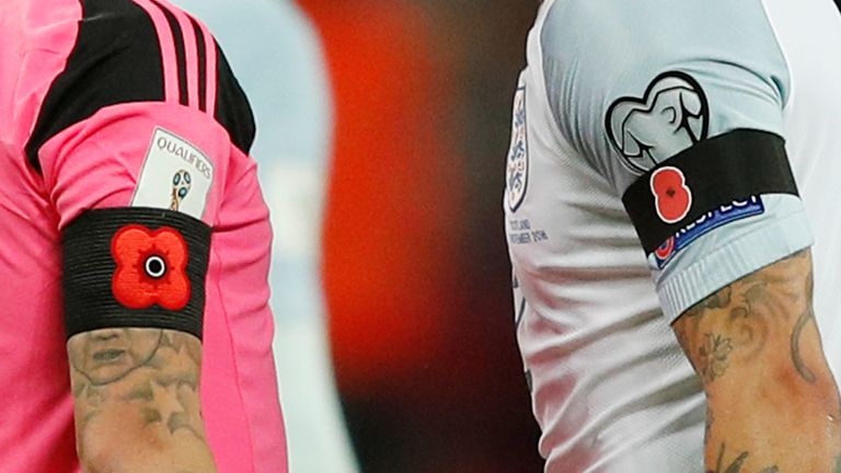 In a picture taken on November 11, 2016 Poppy armbands worn by England's defender Kyle Walker (R) and Scotland's forward Leigh Griffiths (L) to comemorate