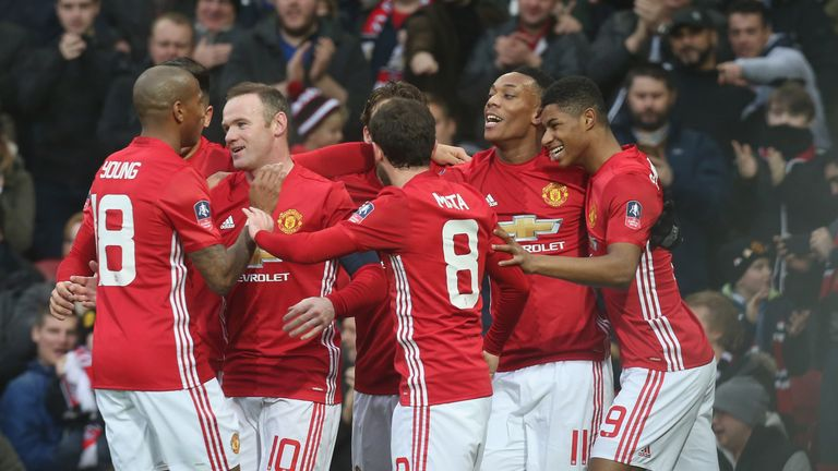 Wayne Rooney is congratulated by team-mates after scoring his 249th goal for the club against Reading