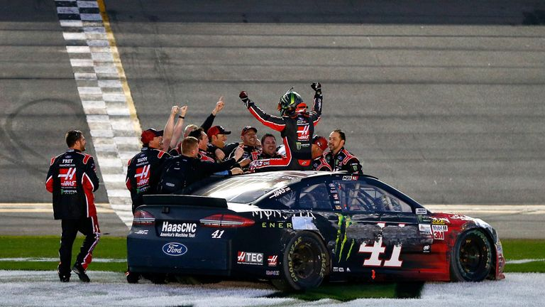Kurt Busch clambers out of his damaged Ford to celebrate with the Stewart-Haas Racing team