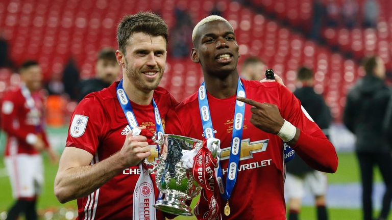 Paul Pogba and Michael Carrick celebrate with the EFL Cup