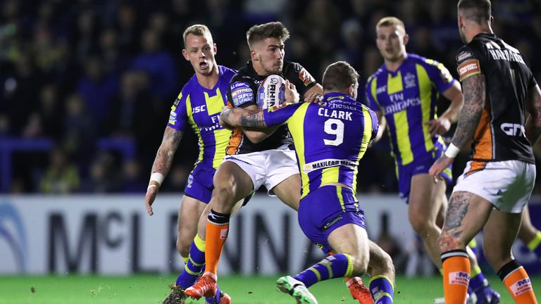 Greg Minikin is tackled by Warrington Wolves' Daryl Clark