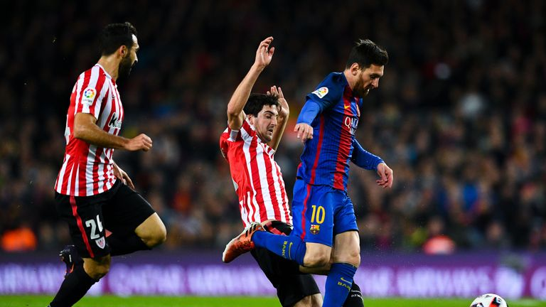 Mikel San Jose tackles Barcelona's Lionel Messi during a game at the Nou Camp