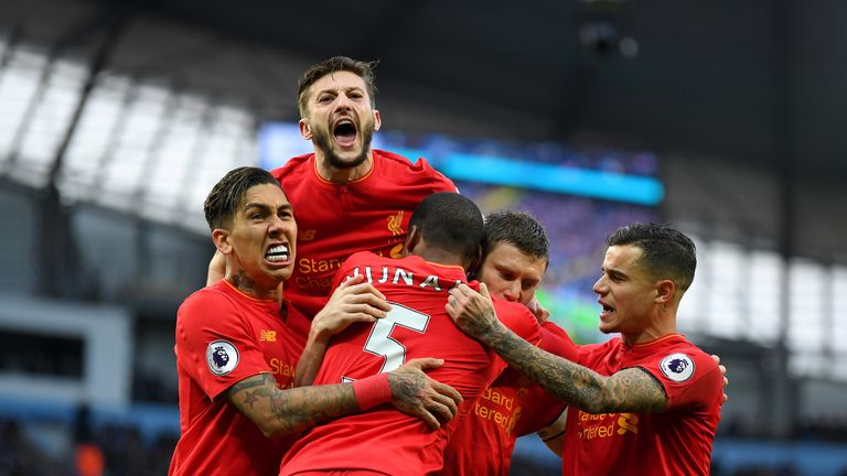 James Milner (centre) celebrates with team-mates after giving Liverpool a 1-0 lead from the spot at the Etihad Stadium on Sunday