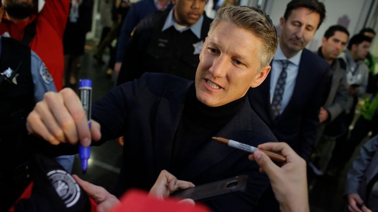 Manchester United midfielder Bastian Schweinstiger signs autographs after he arrives at O'hare International Airport on March 28, 2017 in Chicago, Illinois