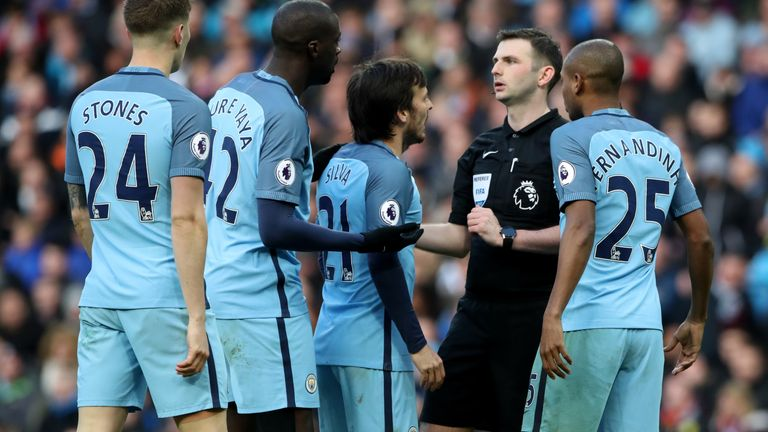 Manchester City players surround referee Michael Oliver after the Liverpool penalty during the Premier League match at the Etihad Stadium