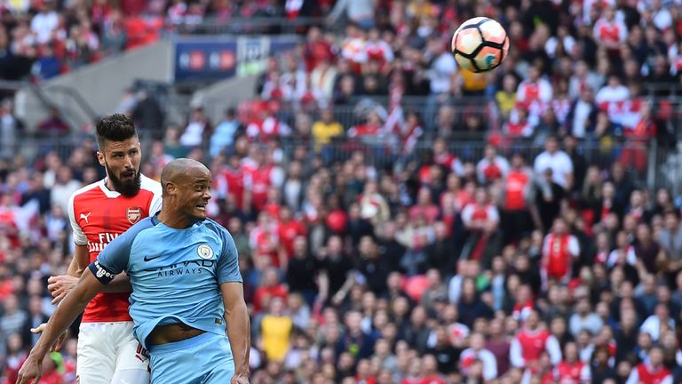 Arsenal's striker Olivier Giroud (L) vies with Manchester City defender Vincent Kompany