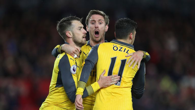 Mesut Ozil (R) celebrates after he scored Arsenal's second goal with Aaron Ramsey (L) and Nacho Monreal (C)