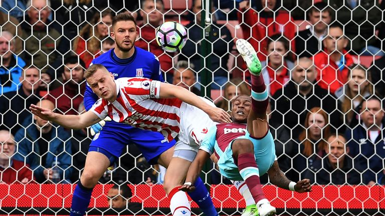 West Ham United's French-born Ghanaian midfielder Andre Ayew (R) tries an overhaed a shot, which is saved by Stoke City's English goalkeeper Jack Butland d
