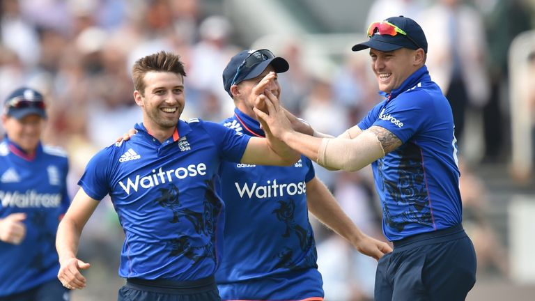 England's Mark Wood (L) celebrates with Joe Root and Jason Roy (R) after taking the wicket of Pakistan's Shoaib Malik (not pictured) during play in the sec