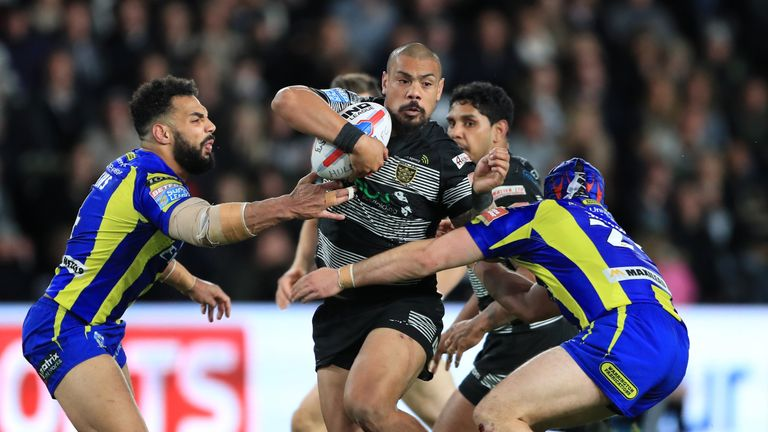 Sika Manu (centre) is tackled by Warrington's Rhys Evans (left) and Benjamin Jullien