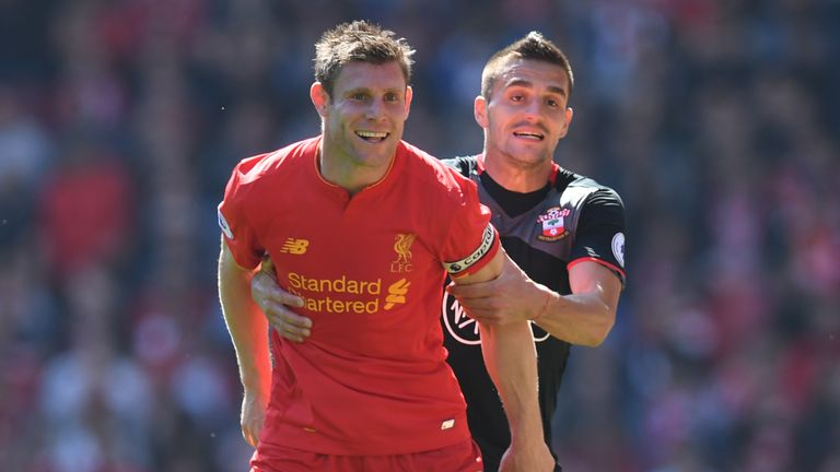 James Milner (left) is held by Southampton's Serbian midfielder Dusan Tadic