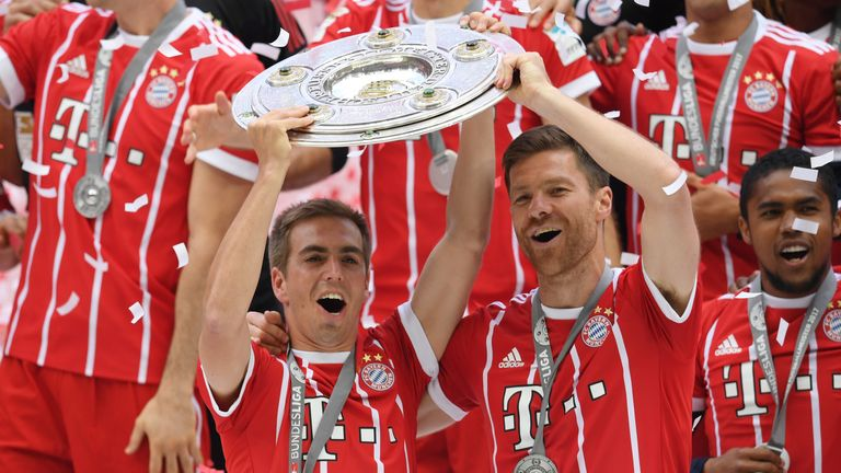 Philipp Lahm and Xabi Alonso lift the Bundesliga trophy after their final game in club football