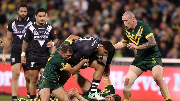 Jason Taumalolo is tackled by Australia's Cameron Smith (left), Trent Merrin and David Klemmer (right)